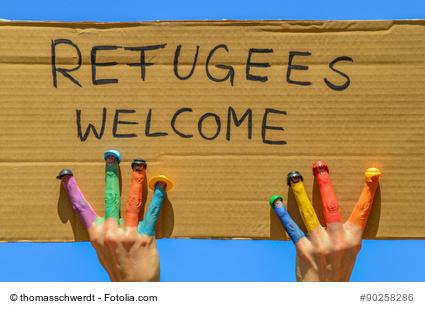 """Refugees welcome - Hnde mit bunten Fingern halten ein Pappschild mit der Aufschrift """"Flchtlinge willkommen"""""""